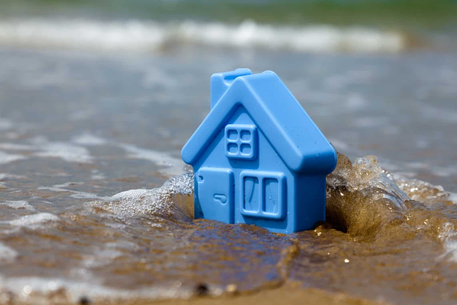 Blue toy plastic house on the sand washes wave